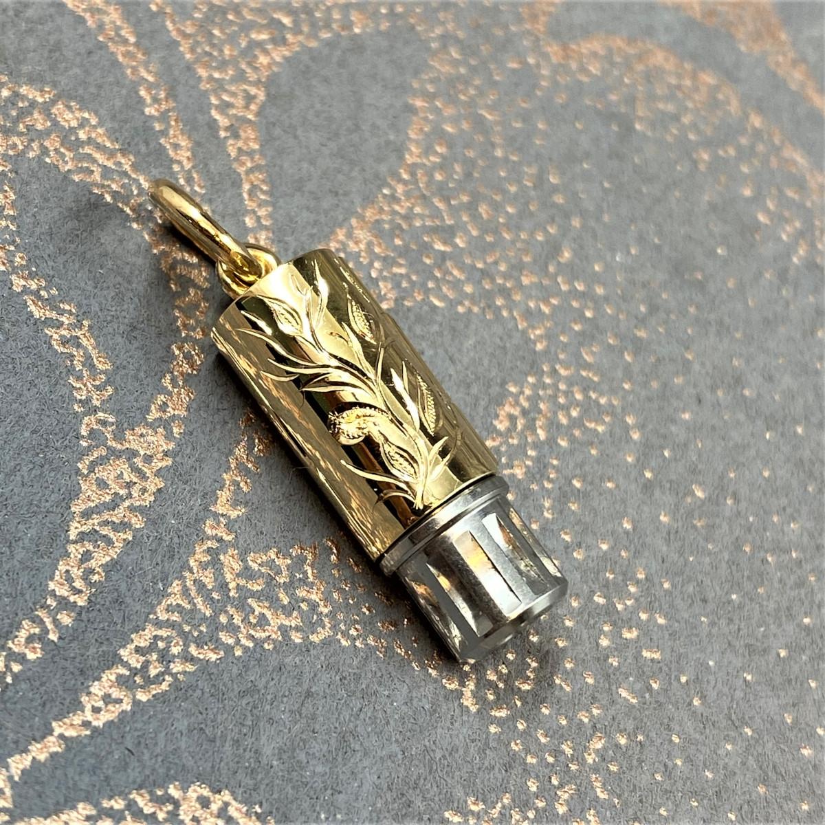 Berlock i guld som gömmer en stålnyckel