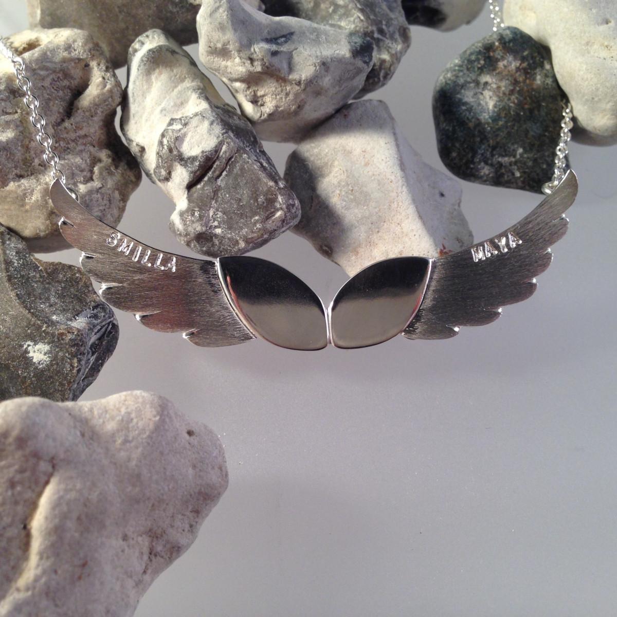 Smycke i silver med stansade namn o änglavingar