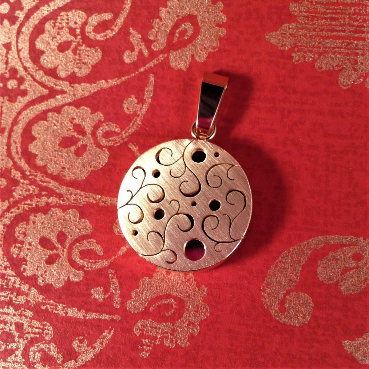 Runt guldsmycke med utsågat ornament